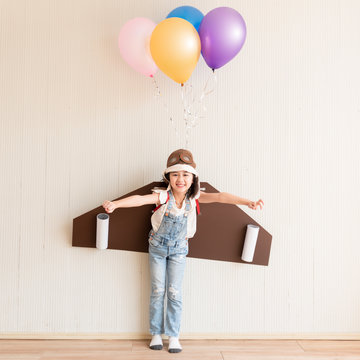 Cute little girl dream of being an astronaut wearing diy wing and balloon as they can make her fly at home