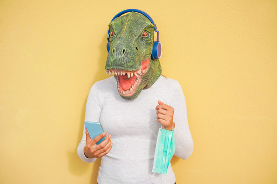 Crazy woman wearing t-rex and holding protection mask while listening music with phone app - Quarantine isolation lifestyle during coronavirus time - Absurd and funny trend concept - Focus on face