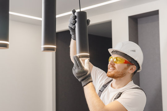 Electrician installs lamp lighting and spot loft style on ceiling