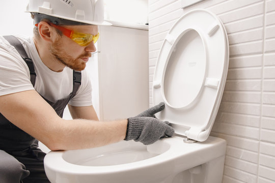 Plumber installing toilet bowl in restroom, work in bathroom
