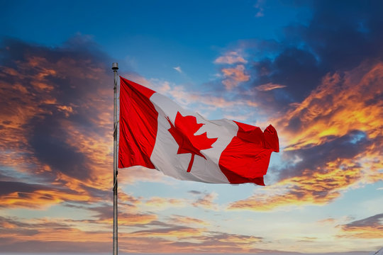 Red and white Canadian Flag Flying at Sunset