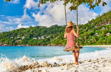 Wall Mural - Woman swinging at tropical beach, Seychelles.