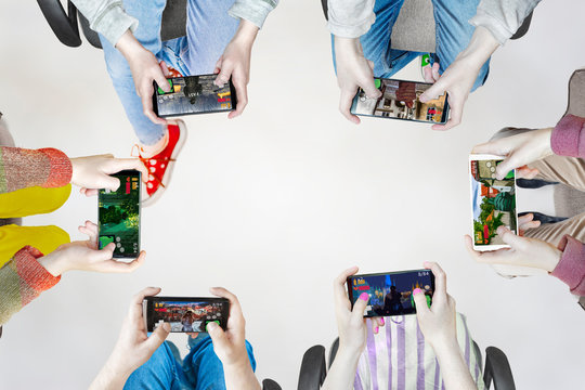 Hands of people playing multiplayer online games with friends on phones while sitting in a bright room. Phone screens are isolated in color. In the center is an empty place for inscriptions.