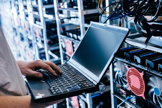 IT specialist working on computer in bitcoin and crypto currency mining farm.