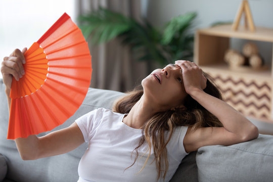 Overheated woman sitting on couch, waving orange paper fan close up, girl feeling unwell, suffering from heating at home, feeling discomfort, hot summer weather or fever, sitting on couch alone