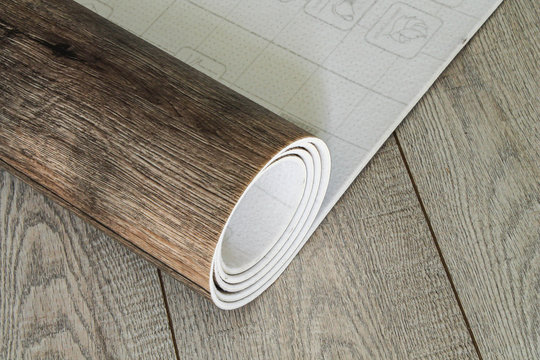 Roll of linoleum with a wood texture. Types of floor coverings.