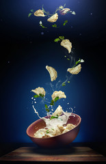 Hot pierogi flying out of the clay bowl with cream and parsley. Some vareniki stay inside the plate. Blue background.