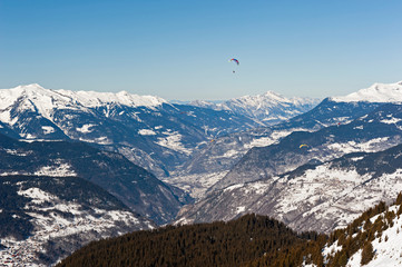 Wall Mural - Panoramic view down a mountain valley with paragliders