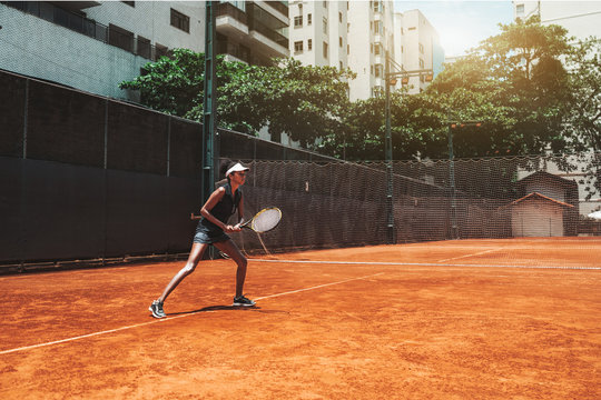 A young slim African-American female plays tennis outdoors in the training court; beautiful biracial sports girl in sports stance ready to deflect tennis ball with the racket in her hands; sunny day