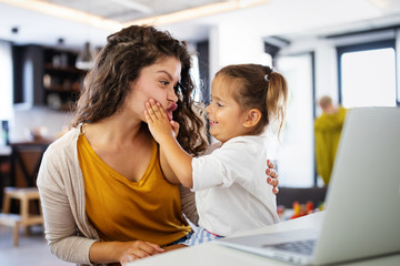 Mother at home trying to work with child distracting her