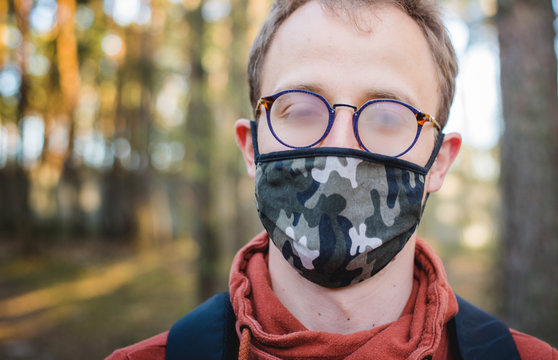 A young white man in a forest wearing a moro pattern cotton mask during a walk with fogging up, fog on eye glasses