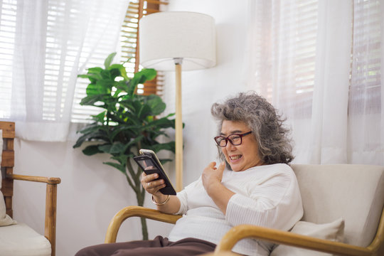 Senior woman old sitting on couch using smartphone browsing, online shopping or video call chat with family. stay safe at home preventing Coronavirus outbreak crisis. aged people connecting technology