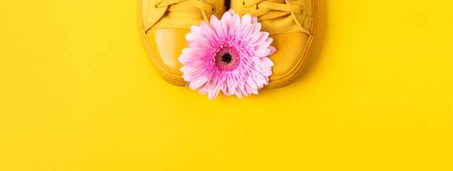 Pair of yellow sneakers and pink gerbera flower. Minimal banner with place for text