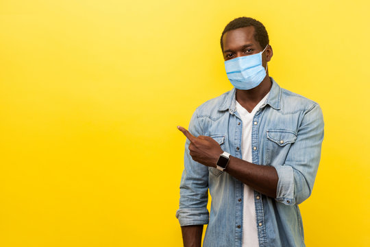 Look, advertise here! Portrait of positive man with surgical medical mask pointing left side and smiling at camera, showing empty space for advertise. indoor studio shot isolated on yellow background
