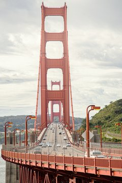 Vertical picture of the Golden Gate Bridge surrounded by hills under a cloudy sky at daytime
