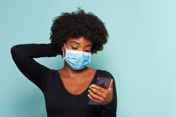 black muher with black power hair wearing protective mask with smartphone in hands