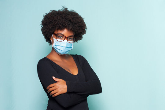 black woman with black power hair wearing protective mask wearing reading glasses