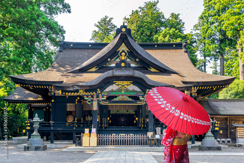 Wall mural Woman wearing japanese traditional kimono with umbrella at katori shrine in Chiba, Japan.
