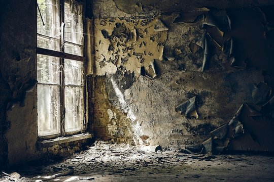 Ruined walls of an abandoned building under the sunlight coming from the broken window