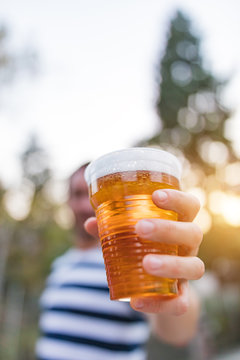 Man holding cold glass of beer outdoors.