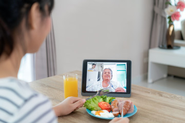 Foto op Canvas Kruidenierswinkel Asian young woman virtual happy hour meeting and eating food online together with her mother in video conference with digital tablet for a online meeting in video call for social distancing.