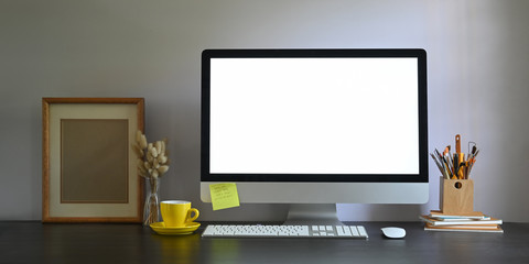 Photo of Workspace blank screen computer monitor putting on working desk and surrounded by picture frame, pencil holder, stack of books, wireless mouse, keyboard, coffee cup and wild grass in vase.