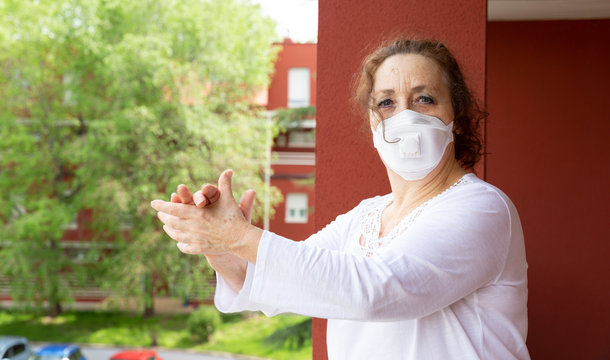 Portrait of old woman wearing medical mask applauding from the balcony in gratitude to the health workers. Confinement by coronavirus.