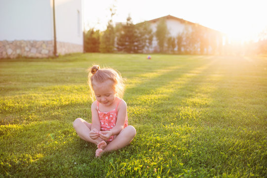 child is sitting on lawn near house. outdoor rest on a summer day. stay at home in rays of setting sun