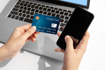 Woman hand holding blue credit card and using modern laptop, typing and texting. against defocus green nature outdoor.  mobile payment ,online shopping concept