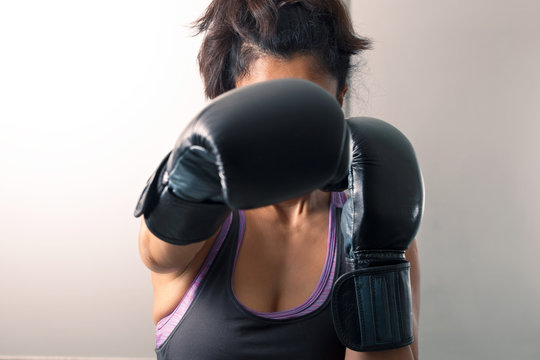 A brunette girl learns fighting techniques of self-defense in boxing gloves.