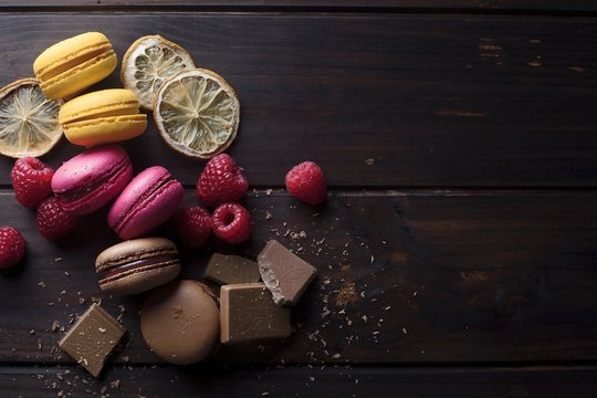 Directly Above Shot Of Macaroons With Raspberries And Chocolate On Table