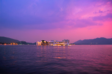 Wall Mural - Romantic luxury India travel tourism - Lake Palace (Jag Niwas) complex on Lake Pichola on sunset in twilight with dramatic sky, Udaipur, Rajasthan, India