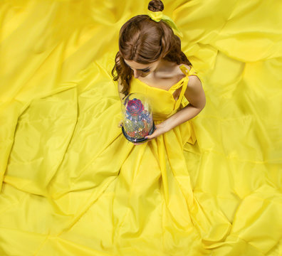 Pretty woman in the yellow long dress closeup with red rose in her hands. Beauty and the beast cosplay art processing.