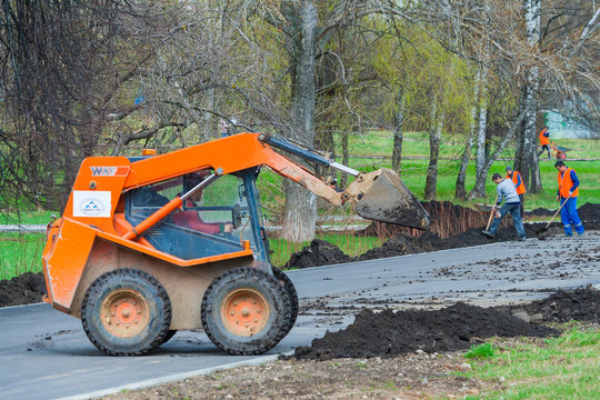 Moscow, Russia, april 2018: Works on the development of the park area. Skid steer unloads black soil (editorial)