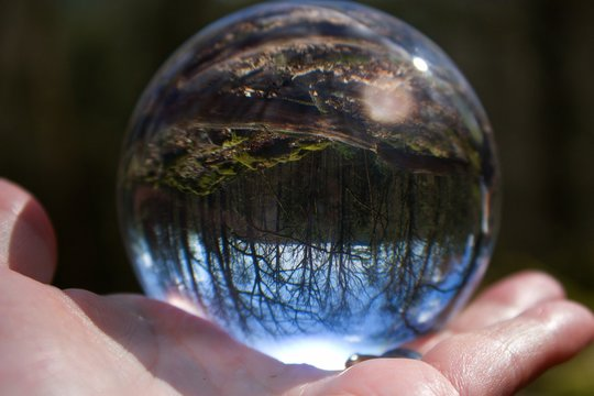 The crystal ball reflects the beautiful nature. The sphere is on the human palm.