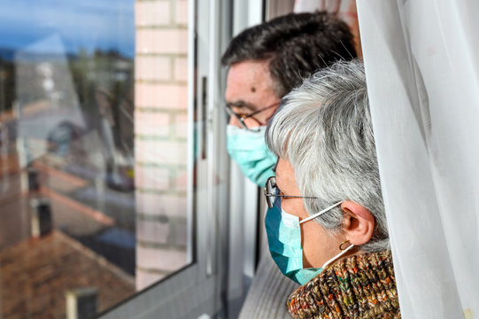 senior couple, with protective face masks, at home looking through the window. Concept of coronavirus quarantine stay home and social distancing. Lockdown people. elderly and retired lifestyle .