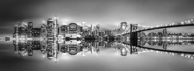 Fototapeten New York .New York City skyline with skyscrapers at sunset on Brooklyn Bridge black and white version