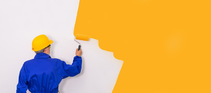 painter with brush painting the wall with work clothes