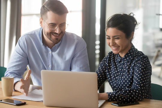 Cheerful hindu woman caucasian man multi-ethnic colleagues working together sit at desk look at computer screen discuss new project search solutions joking to increase effective communication concept