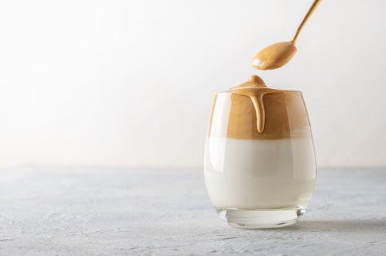 Korean drink Dalgona coffee in glass with milk with and instant coffee on white. Copy space.
