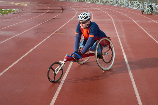 Handicapped sportsman in helmet and sunglasses sitting in racing wheelchair