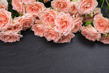 Tuinposter Lelie Fresh pink roses on a black background made of natural stone. Copy space
