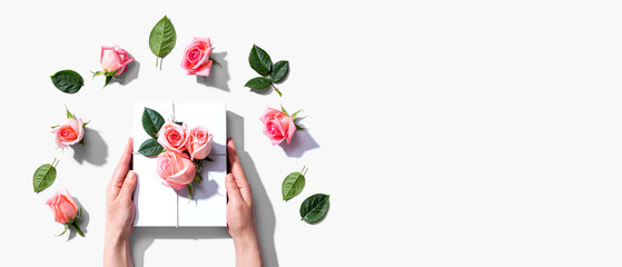 Photo sur Toile Roses Female hands holding a gift box with pink roses overhead view - flat lay
