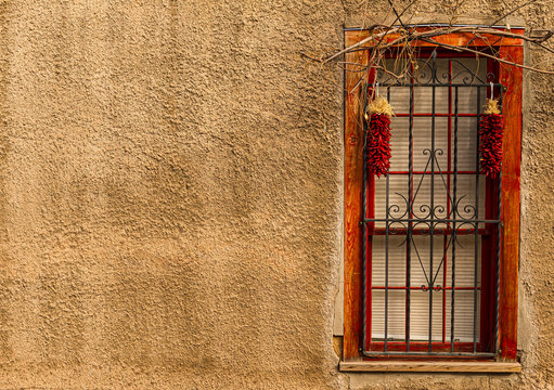 Window With Bars On Adobe Wall With Ristra