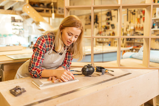 hardworking caucasian woman woodworker make drawings, young lady loves her job in factory