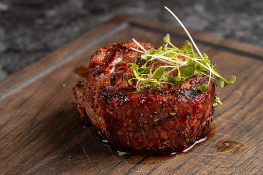 Fried beef fillet medallion steak close up on a wooden cutting board