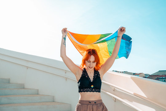 Woman holding the gay pride flag as she walks down a flight of stairs