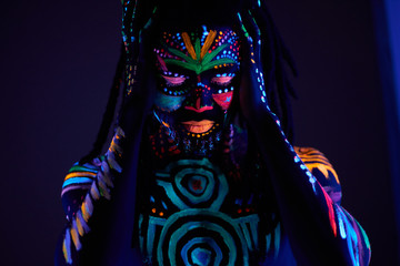 african man with fluorescent body art suffer from headache, hold head, stand with closed eyes. UV body art