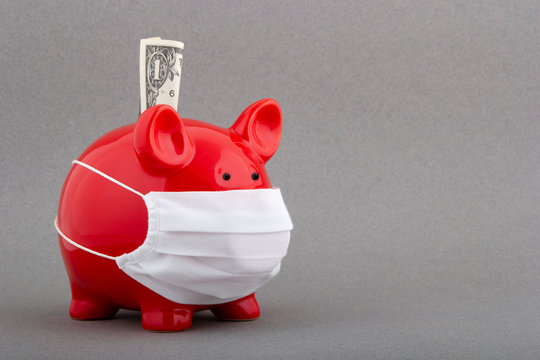 Piggy bank with medical mask as a symbol for medical expenses on grey background. Money saving concept in time of coronavirus pandemic.