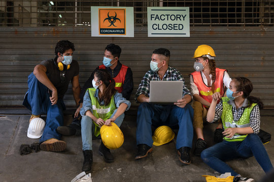industrail background of diverse factory workers, labors and engineer with wearing medical mask sitting together in front of closed factory with layoff annoucement from covid-19 pandemic